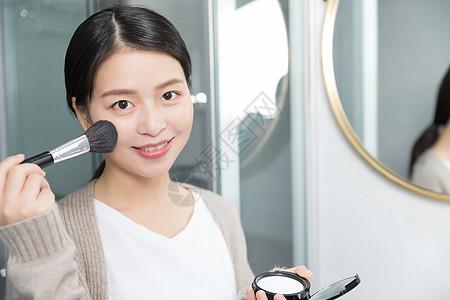 正在化妆补妆的年轻女性图片