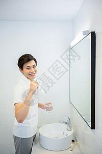 年轻男性在浴室刷牙图片