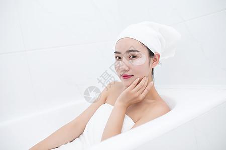 包着头发坐在浴缸里敷眼膜的年轻美女图片