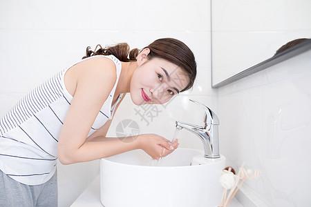 早起在洗漱台洗脸的年轻人图片