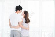 年轻情侣在窗边相拥拥抱图片