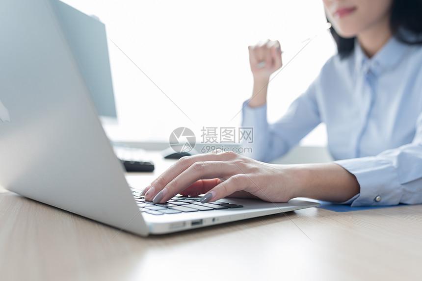 正在打字使用电脑工作手部特写图片