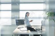 在办公室喝咖啡的自信职业女性图片