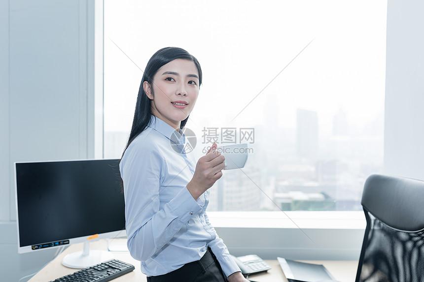 职业女性工作照片_工作微笑办公室在办公室喝咖啡的自信职业女性图片在办公室喝咖啡的自