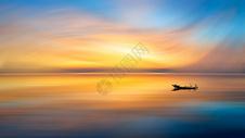 唯美夕阳下的大海和归航的渔船图片
