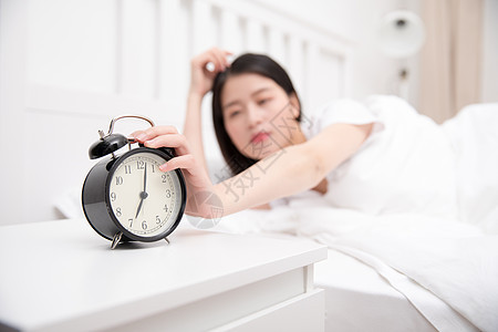 被闹钟吵醒的年轻美女图片