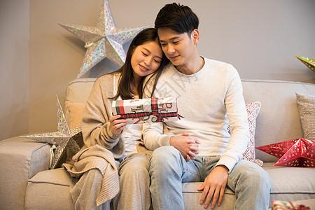 拿着礼物坐在客厅的情侣图片