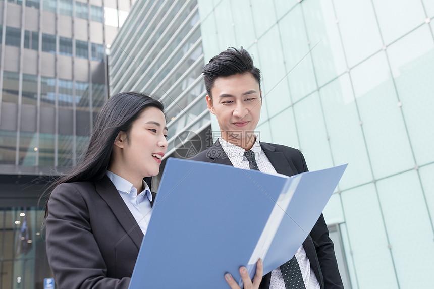 拿着文件夹边走边交流的商务人士图片