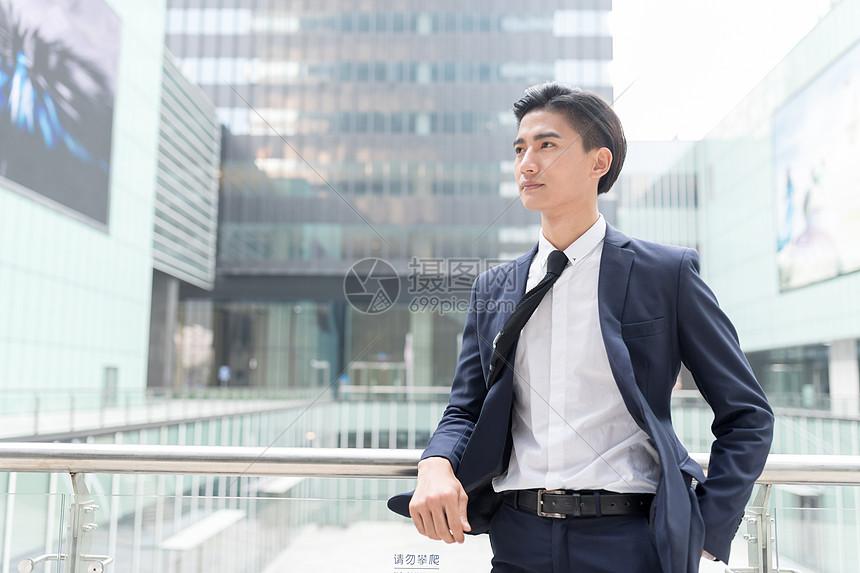 站在商务楼写字楼下眺望远方的商务男士图片