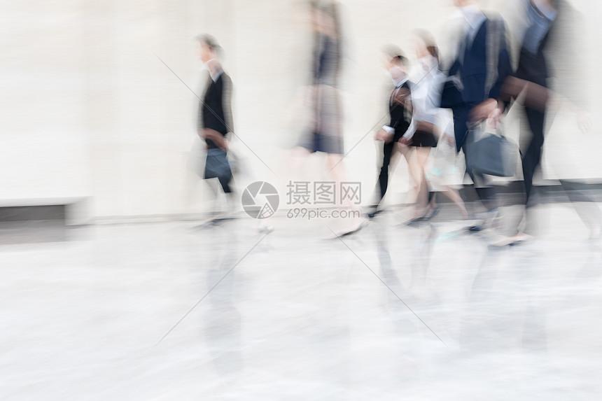 写字楼里走路的商务人士身影图片