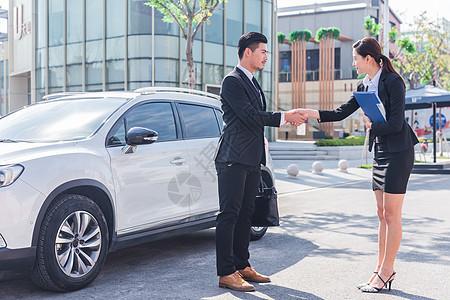 车前商务人士合作握手图片