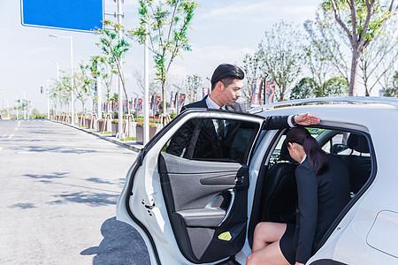 专车司机给商务女士挡车顶图片