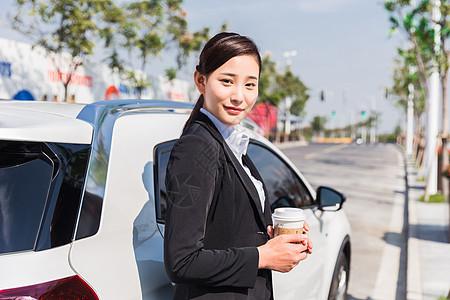 商务女士拿咖啡靠在车上休息图片