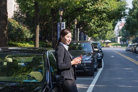 商务女士拿着手机靠在车上图片