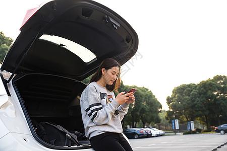 美女在后备箱低头看手机图片