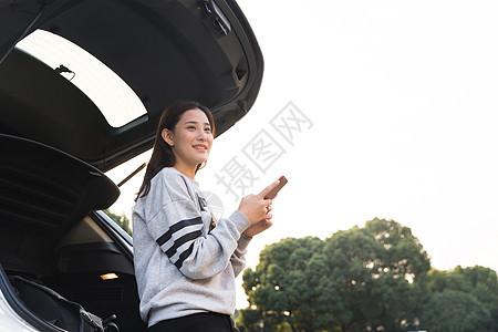 美女在后备箱拿着手机看远方图片