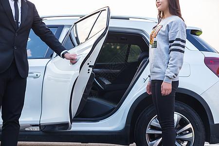 男性司机为女性乘客开车门图片