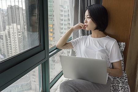 女子坐在飘窗使用电脑图片