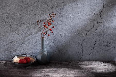 水泥墙角的花瓶和水果碟图片