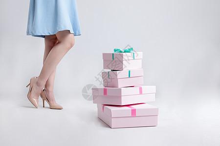站在礼物盒旁边的年轻美女图片