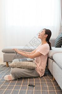 家居女性靠着沙发玩电脑图片