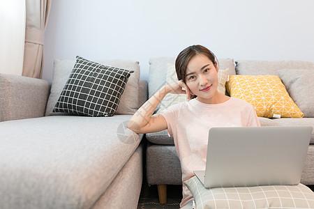 年轻美女靠着沙发玩电脑图片