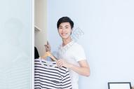 帅气男子打开衣柜拿衣服图片