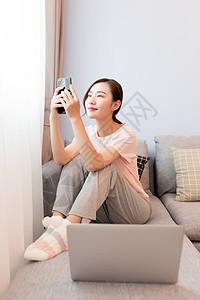 家居女性坐在沙发上玩手机图片