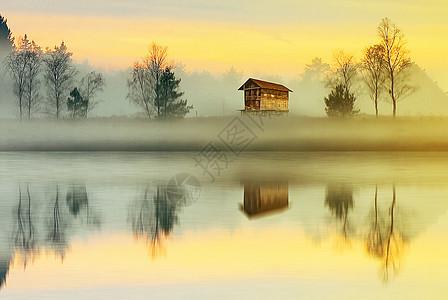 清晨乡村充满雾气的湖边倒影图片
