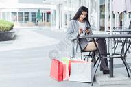 年轻美女购物休息看手机图片