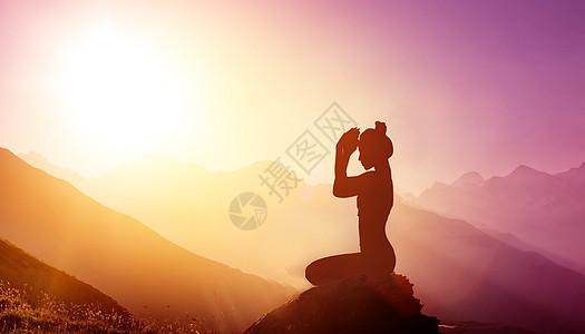 山顶上锻炼瑜伽的女性图片