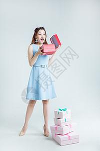 年轻女性手拿礼物盒棚拍图片