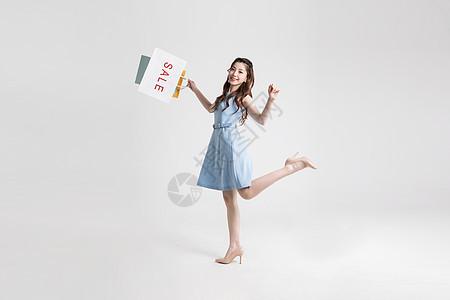 提着购物袋开心购物的年轻美女图片