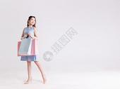 惊喜的拿着购物袋的年轻女性图片
