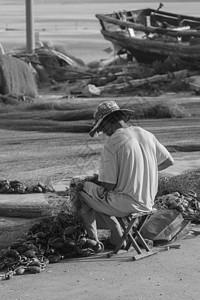 渔民在修补渔网图片
