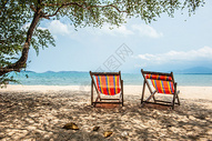沙滩边的彩色躺椅图片