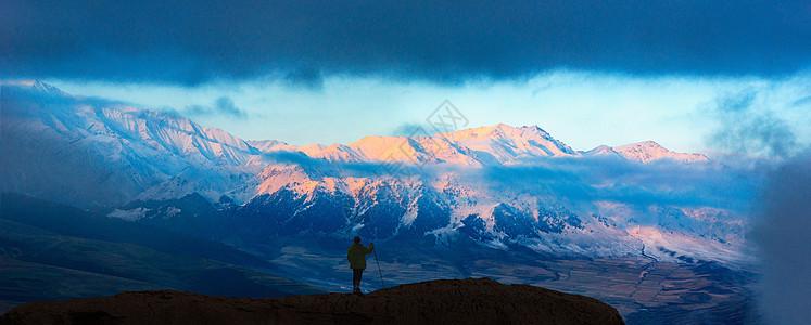 日照雪山与登山者图片