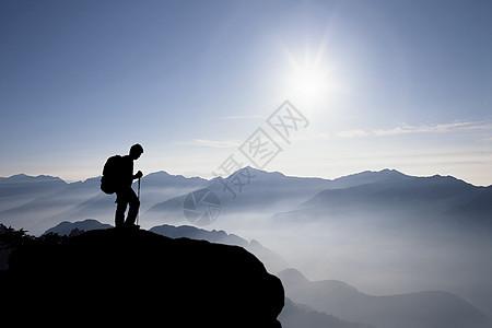 登上山顶俯视群山的人图片
