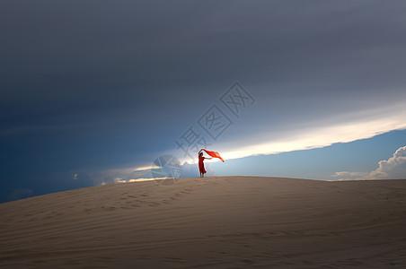 一望无际沙漠里的红衣美女背影图片