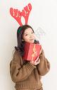 开心地拿着圣诞礼物的女生图片