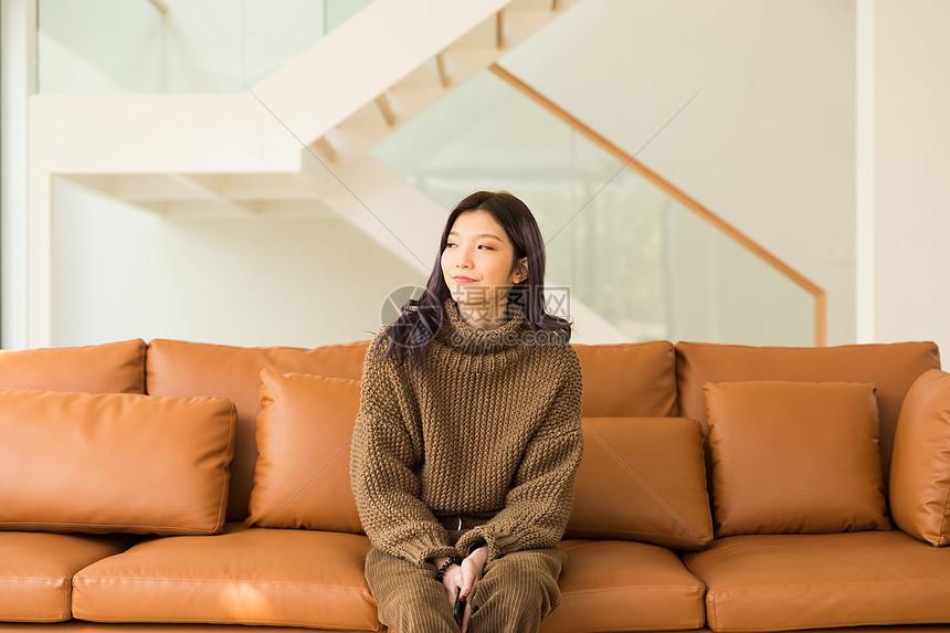坐在客厅沙发上的年轻女性图片