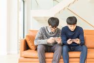坐在客厅里玩手机的年轻人图片