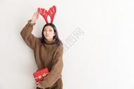 手拿礼盒带着鹿角的圣诞女性人像图片