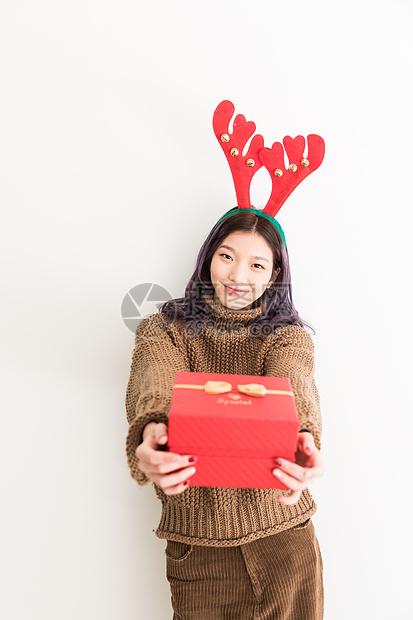 圣诞节拿着礼物的年轻女性图片