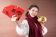 女性手拿红包储蓄罐图片
