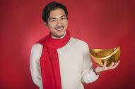 新年男士手拿金元宝图片