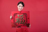 春节穿旗袍的女孩手拿福字500773238图片