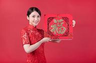 春节穿旗袍的女孩手拿福字500773241图片