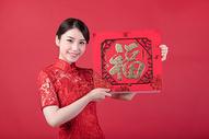 春节穿旗袍的女孩手拿福字500773242图片