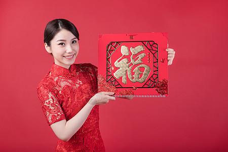 春节穿旗袍的女孩手拿福字图片